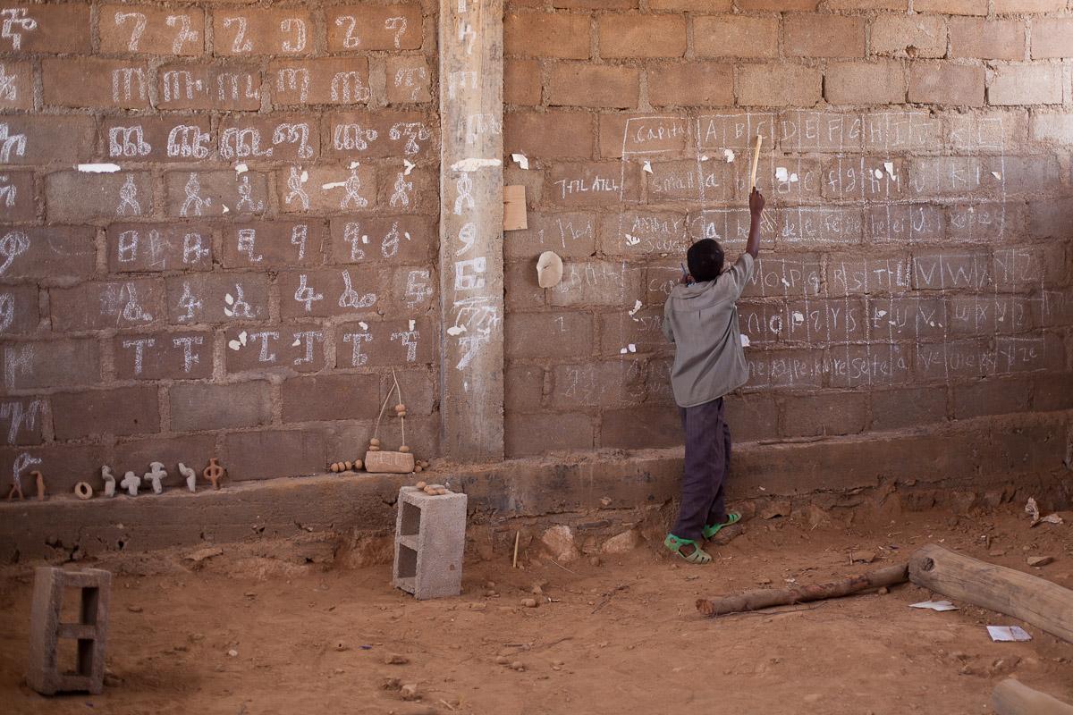 Ein Junge der Sifra Jeganu Schule übt das Alphabet an der Wand.