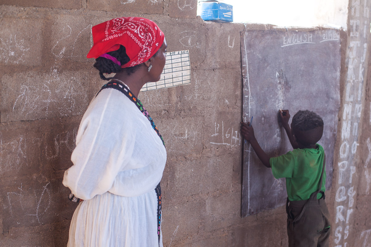 Die Lehrerin schaut auf einen Schüler der gerade auf die Tafel schreibt.