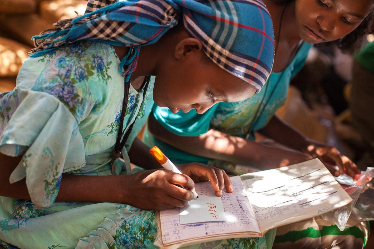 """Ein Mädchen schreibt eine """"Dankeskarte"""" für die Spender"""