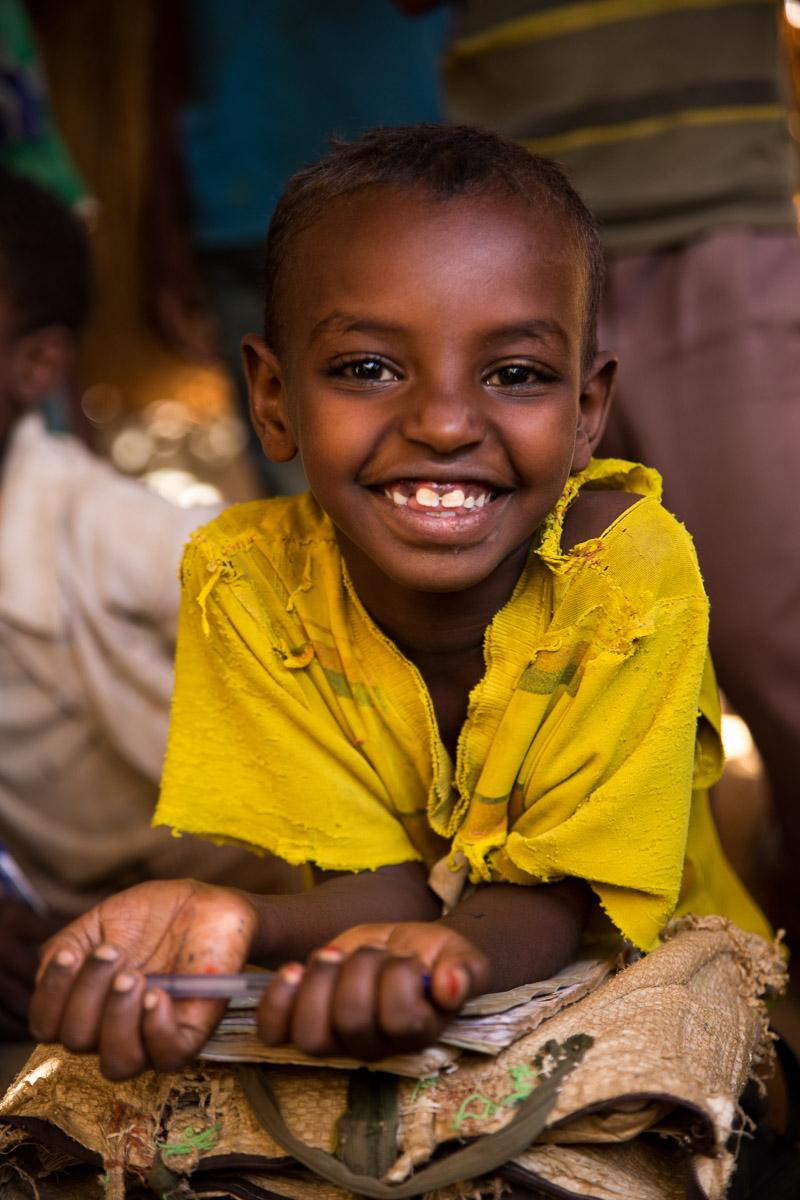 Ein süßer Schüler lächelt die Kamera an.